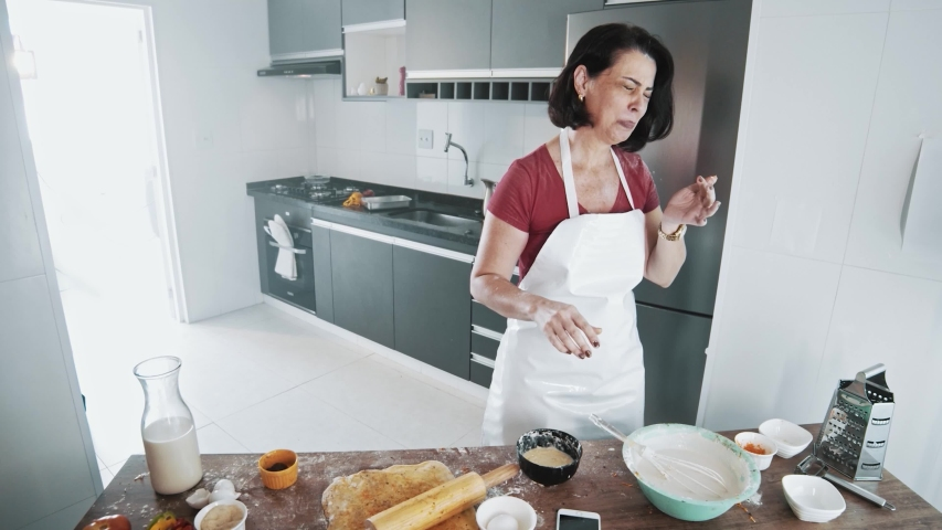 Dissatisfied Woman Cooking and Looking. Housewife middle-aged woman tasting recipe she is preparing. Bad food. Cinematic 4K.   Shutterstock HD Video #1041117160