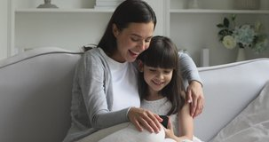 Cute little small kid child daughter having fun with adult mum enjoying using smart phone showing funny face mask app on modern gadget cellphone looking at mobile screen laughing sit on sofa at home