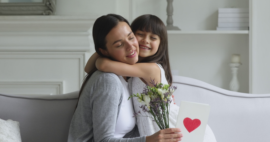 Cute little funny kid child daughter congratulating happy young mom with mothers day concept presenting spring flowers and greeting card embracing affectionate mum having fun sit on sofa at home