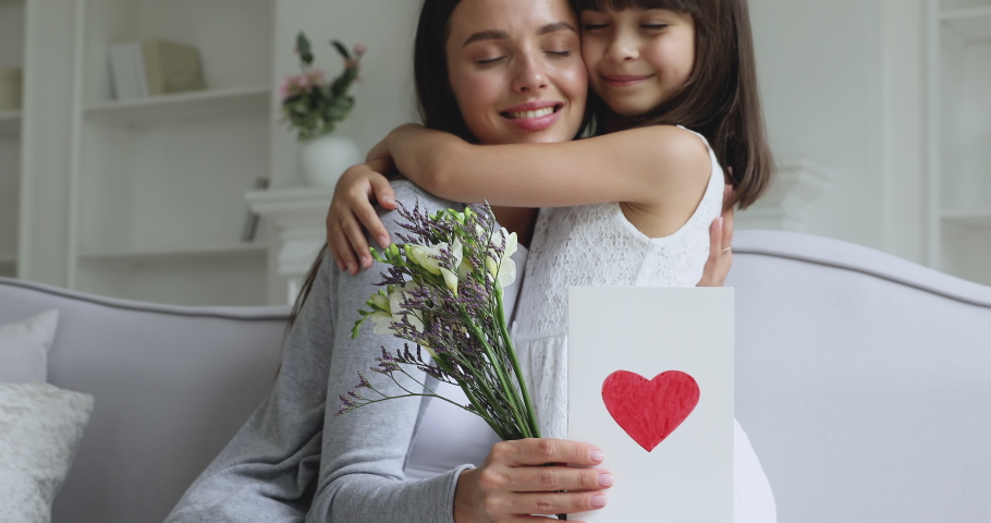 Loving cute small kid child daughter hugging kissing happy young mum congratulating with mothers day concept embracing grateful mommy holding spring flowers and greeting card with red heart at home Royalty-Free Stock Footage #1041120058