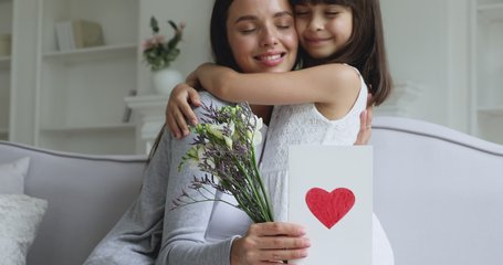 Loving cute small kid child daughter hugging kissing happy young mum congratulating with mothers day concept embracing grateful mommy holding spring flowers and greeting card with red heart at home