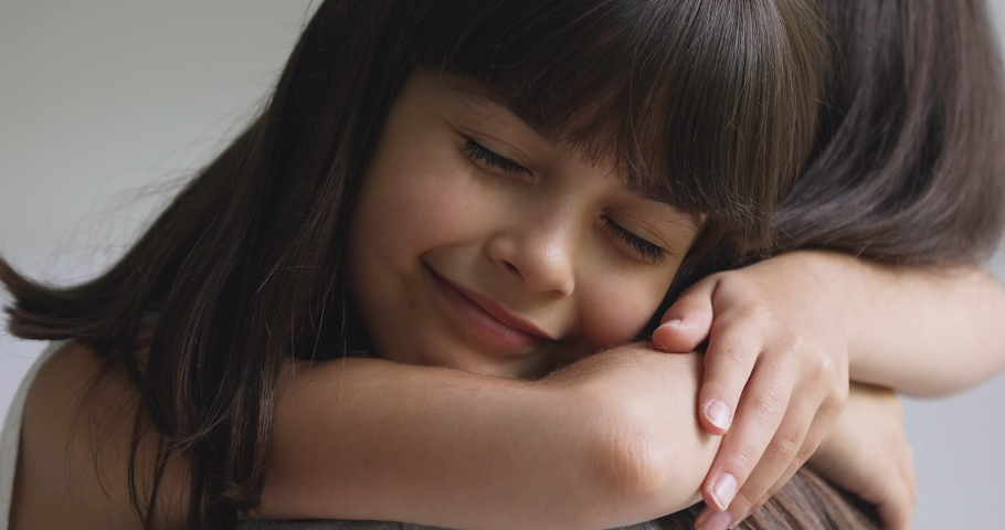 Happy cute affectionate adopted little kid girl hugging foster care parent mother with eyes closed, adorable small child daughter embrace mum cuddling enjoy tender sweet moment concept, close up view | Shutterstock HD Video #1041120067