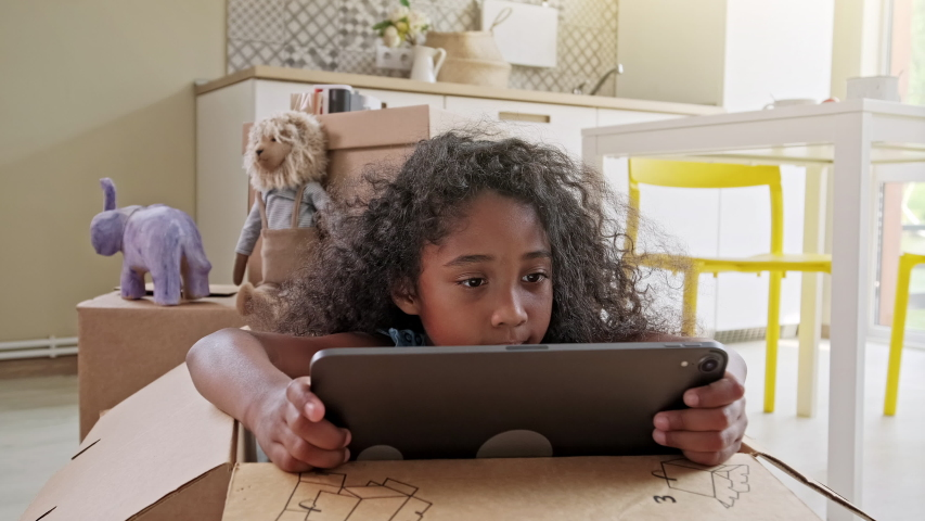 Young black girl with a fun afro hairstyle sitting in a box at home browsing the internet on a tablet computer Royalty-Free Stock Footage #1041120964