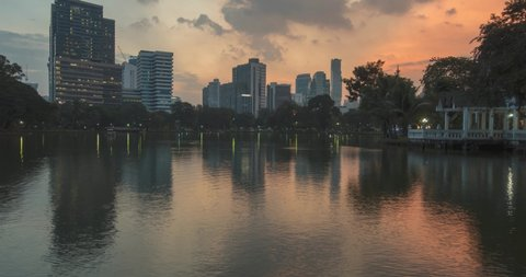 4K UHD of night city landscape with big lake, green trees and lights. Autumn or summer sunset weather with clouds and water reflections. Lumpini Park, Bangkok, Thailand.