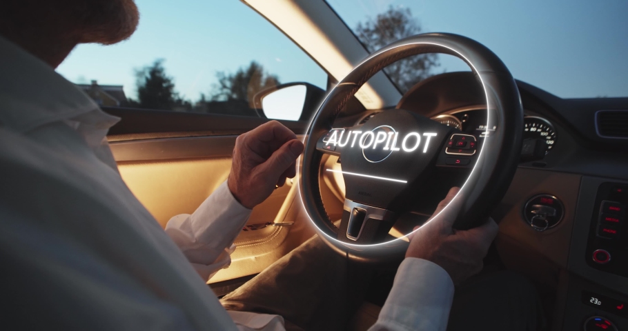 A man driving futuristic car activates autopilot on augmented reality hologram hud. Vehicle starts autonomous self-driving. Hands free system. Concept of Driverless Future Technology in transport.