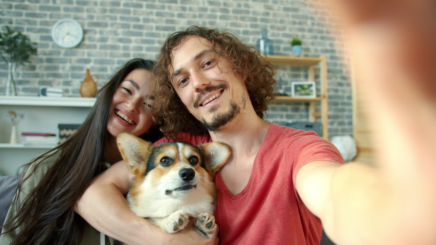 Joyful girl and guy taking selfie with corgi dog having fun making funny faces showing hand gestures thumbs-up and v-sign. Youth and technology concept.