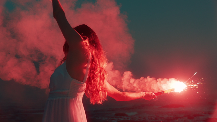 woman waving red flare dancing on beach at dawn expression creative freedom burning distress signal firework Royalty-Free Stock Footage #1041156109