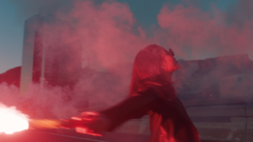 woman dancing with red flare in city at sunrise rebellious girl protesting in street with firework female millennial freedom movement Royalty-Free Stock Footage #1041156325