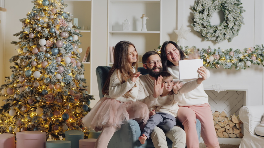 Happy young family with two children sitting on the armchair in the living room , online video chatting. The room is decorated with a Christmas tree and garlands. Everyone waving their hands while