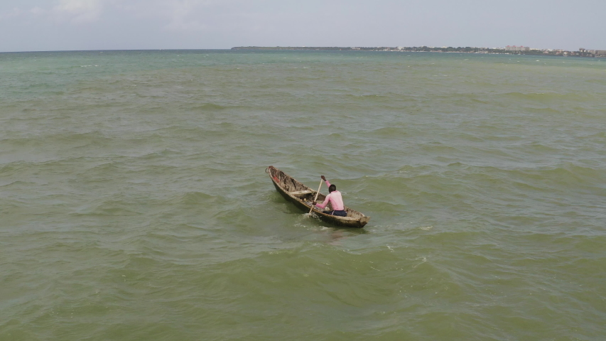 A man paddling a wooden canoe boat against waves and wind near the coast of Dar es Salaam on a sunny day, Tanzania