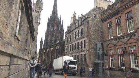 Edinburgh, Scotland UK - 17 March, 2015 Tourists in warm clothes visit Edinburgh, walk on the street, medieval city