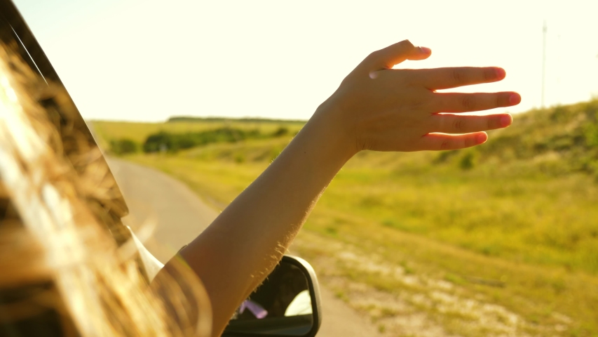 Girl with long hair is sitting in front seat of car, stretching her arm out window and catching glare of setting sun.   Shutterstock HD Video #1041169873