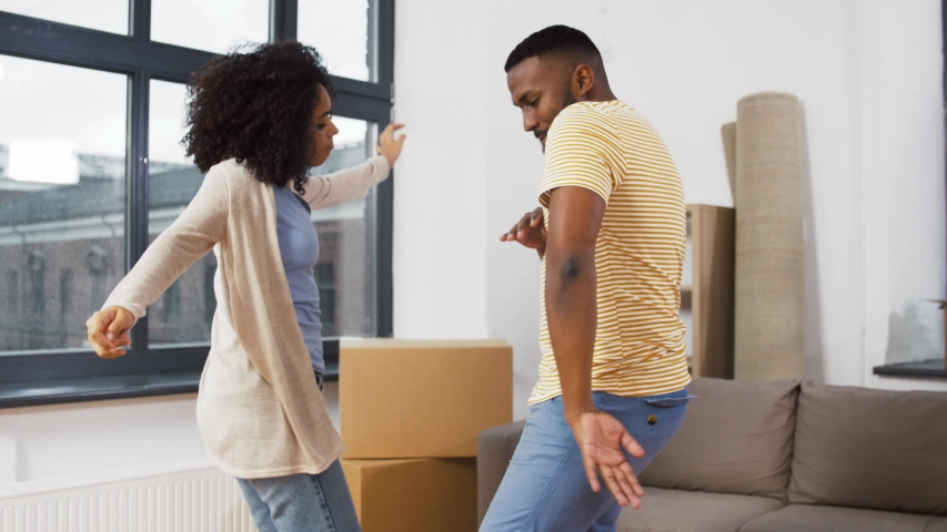 moving, repair and real estate concept - happy african american couple dancing at new home #1041194830
