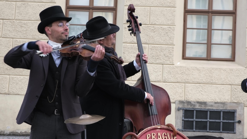 PRAGUE, CZECH REPUBLIC - OCTOBER, 2019.  Group of street musicians dressed in old-fashioned suits and hats play the violin, cello and accordion in tourist center of old city. Footage with Sound.