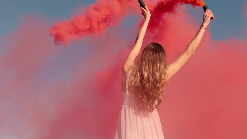 Woman waving pink smoke bomb on beach at sunrise slow motion