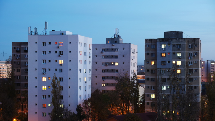 Time lapse of windows light on a multi-storey apartment building from blue hour to night. Buildings with renovated exteriors near old communist era buildings, at night.