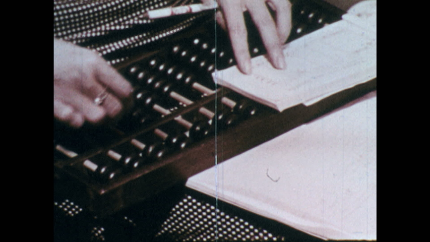 1960s: CHINA: girl calculates using abacus. Figuring on abacus to work out bill