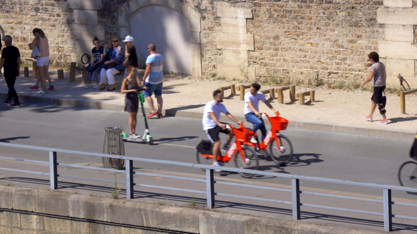 Paris, France- July 2019 : Parisians strolling and biking along the banks of the Seine on a beautiful summer day during Paris Beach