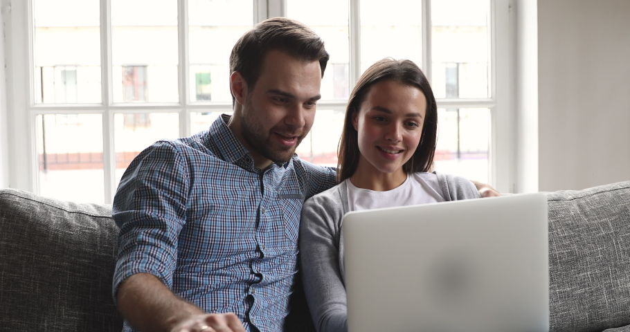 Happy young family couple talking bonding using laptop looking at screen sit on sofa, smiling husband and wife embracing buying choosing goods online do internet shopping order with delivery at home Royalty-Free Stock Footage #1041220450