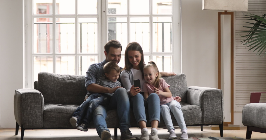 Happy family of four enjoy using smartphone technology relax sit on couch at home, relaxed parents father mother and cute little kids children watch funny social media video on mobile phone together