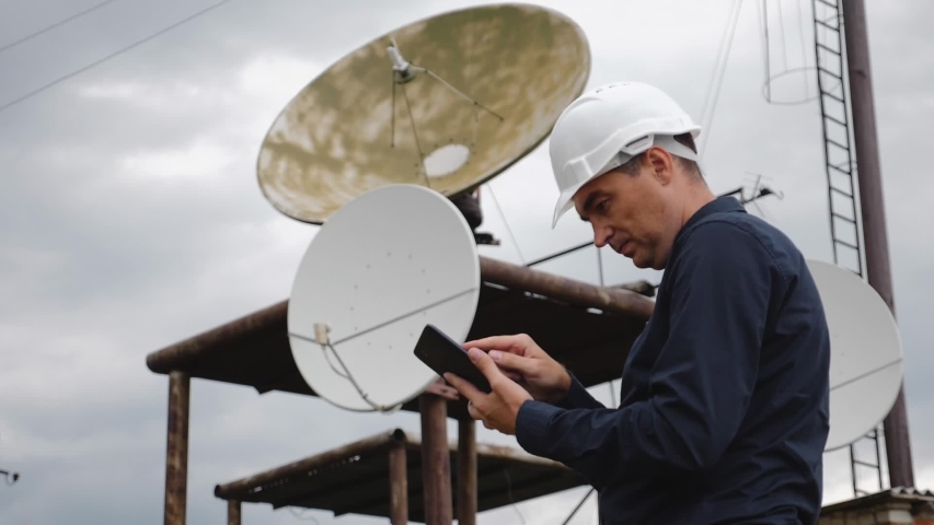 Helmet engineer and with a tablet standing on the roof of the building working with a satellite dish. Successful quality performance of tasks. The concept of repair and installation services | Shutterstock HD Video #1041222208