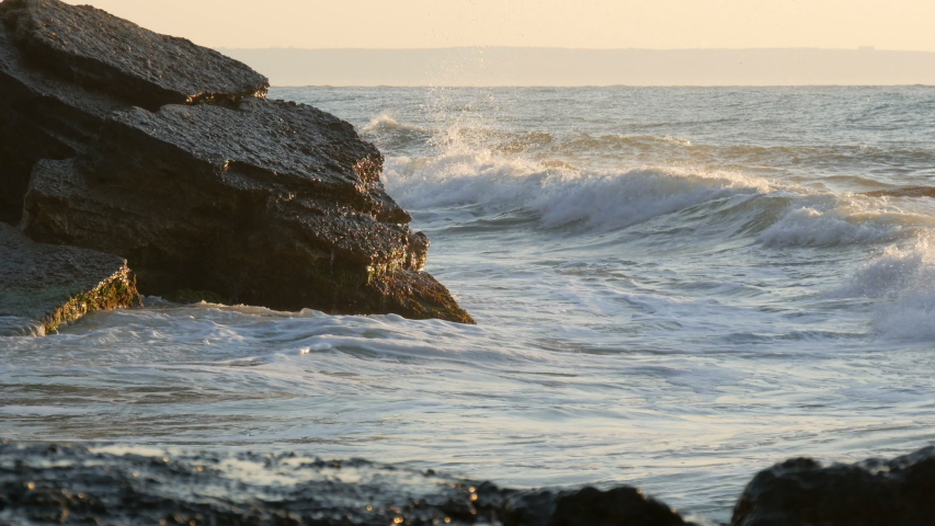 Beautiful sunset or sunrise over the sea. Big strong waves crash into huge rocks. Storm at sea. Big waves break on the rocky shore, white foam on the water. Black Sea, Bulgaria Royalty-Free Stock Footage #1041234871