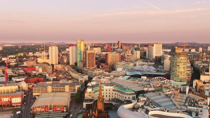 birmingham aerial view drone flying backwards from bullring grand central at sunrise