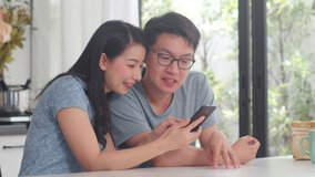 Young Asian couple enjoy shopping online on mobile phone at home. Lifestyle young husband and wife happy buy ecommerce after have breakfast in modern kitchen at house in the morning concept.