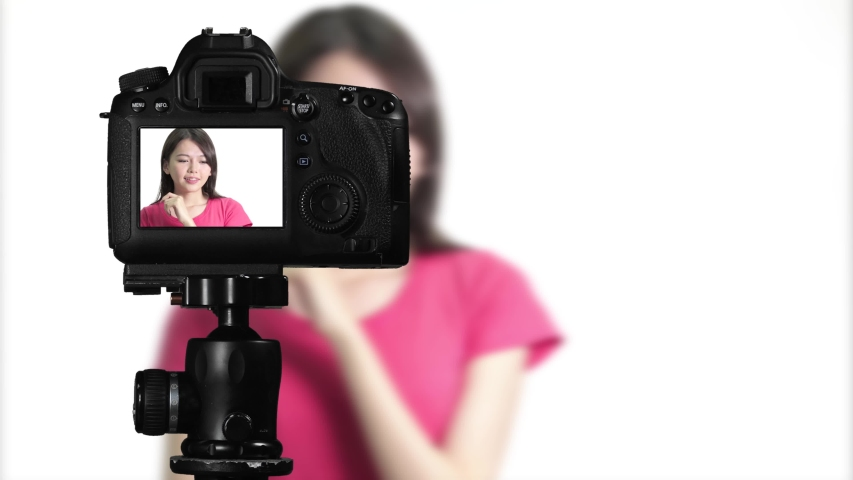 Asian American woman having eureka moment on camera, creating content for social media vlog, behind camera shot