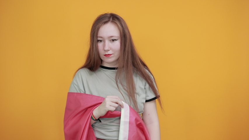 Boring young caucasian woman posing isolated on orange background in studio wearing casual shirt, keeping finger on head covered bisexual flag | Shutterstock HD Video #1041258703