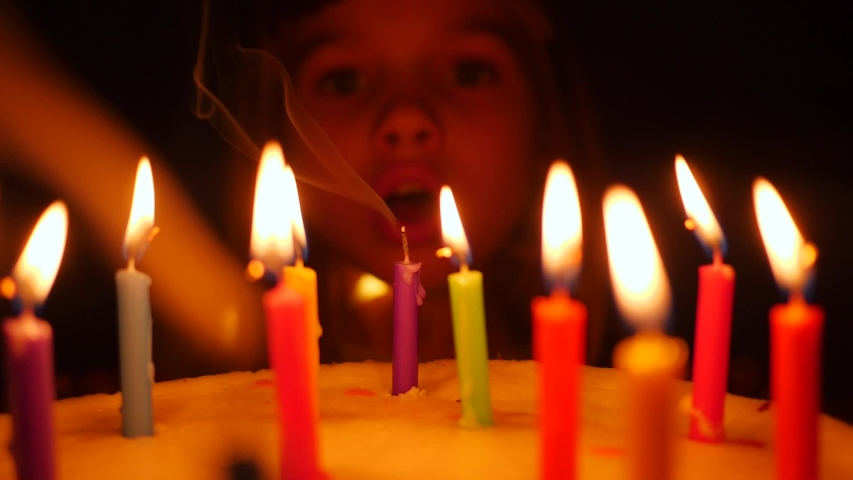 Cute little kid girl enjoy blow out candles on birthday cake celebrating at home slow motion