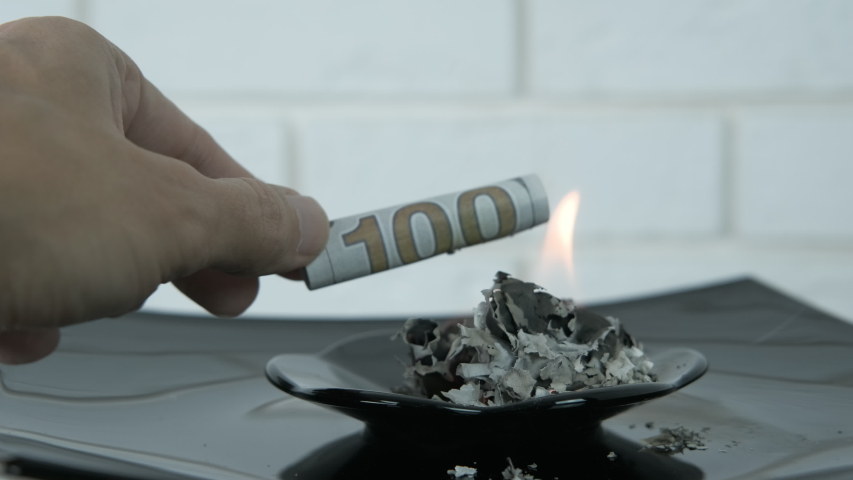 Burning dollars. A view of male`s hand putting dollars in the fire on the black plate with ashes from the money. | Shutterstock HD Video #1041263407