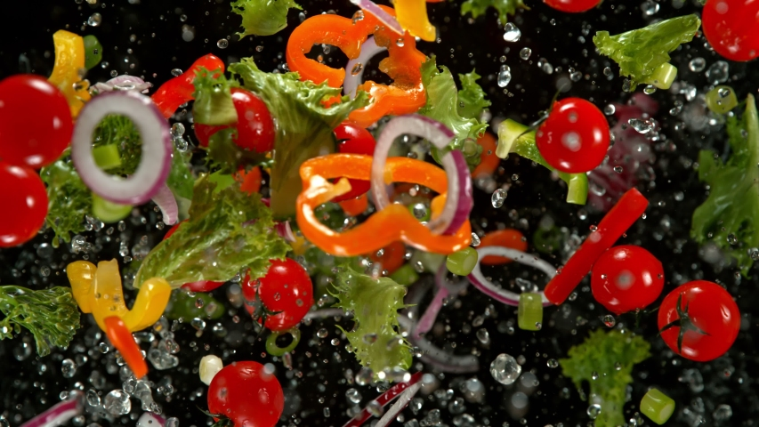 Super Slow Motion Shot of Flying Cuts of Colorful Vegetables and Water Drops on Black background at 1000fps. | Shutterstock HD Video #1041266815