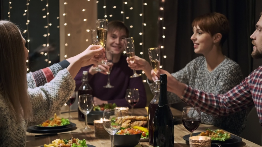 Friends holiday party dinner at home around the table. Celebrate Christmas. Five people eat, drink champagne, talk and laugh. Christmas eve. | Shutterstock HD Video #1041268051