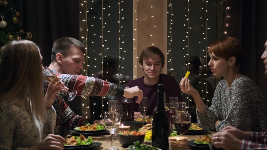 Friends holiday party dinner at home around the table. Celebrate Christmas. Five people eat, drink champagne, talk and laugh. Christmas eve. | Shutterstock HD Video #1041268063