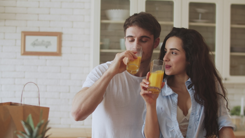 Happy couple drinking orange juice at home kitchen. Closeup sexy couple flirting at home. Young married couple hugging kitchen.