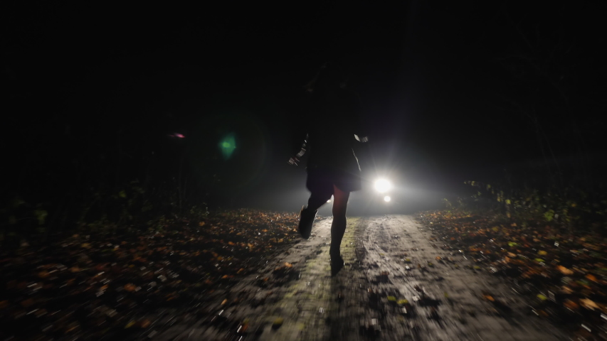 A frightened girl quickly runs away from a car following her along a country road at night. Silhouette of a running girl in the headlights of a car.