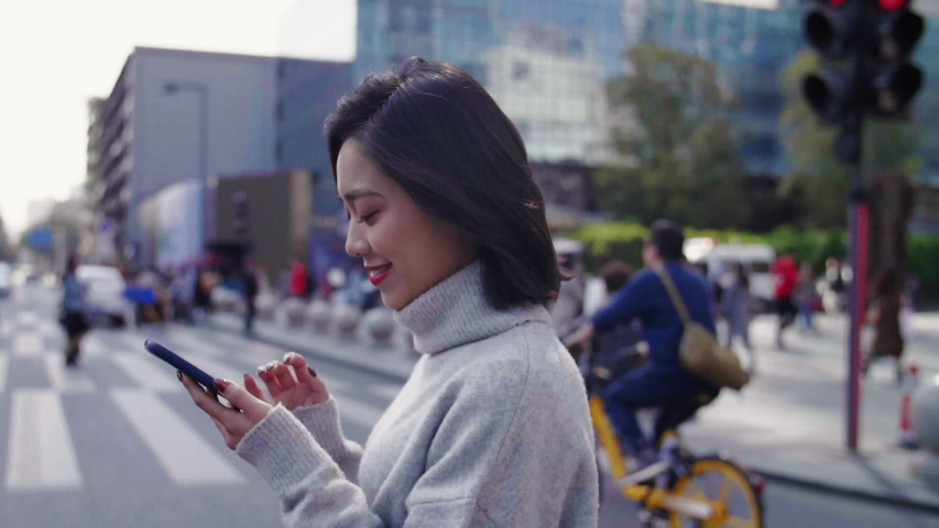 Slow motion Cheerful asian woman looking at mobile phone walking in the street to the office business urban people commuter with cellphone in hand