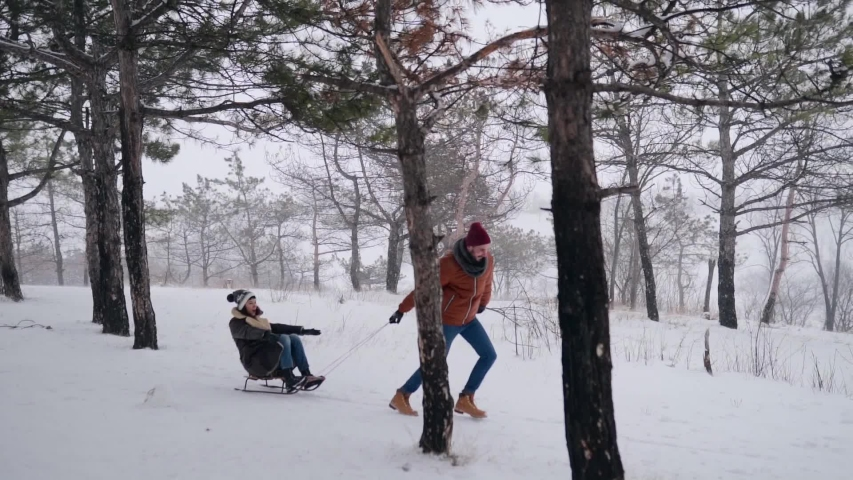Lovely couple sledding on snowy winter day. Man pull sled with girlfriend on snowfall. Woman have fun and sledge outdoors with boyfriend. People sleigh ride and enjoy Christmas vacation. Slow motion.
