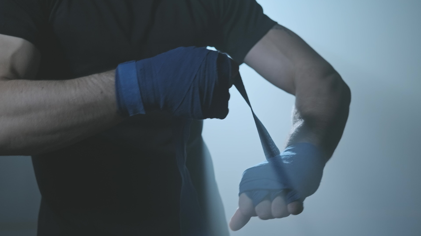 Male boxer wrapping hands before fighting in slow motion. Close-up of young athlete getting ready for fight. Man preparing. Sport concept in 4K, UHD | Shutterstock HD Video #1041321538