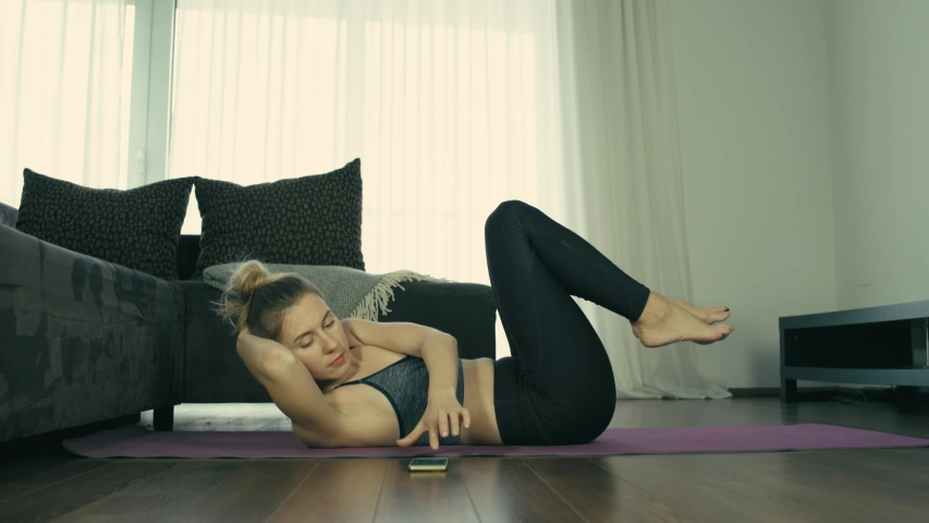Young woman doing sports at home, Female fitness training in sportswear in the room  | Shutterstock HD Video #1041340711