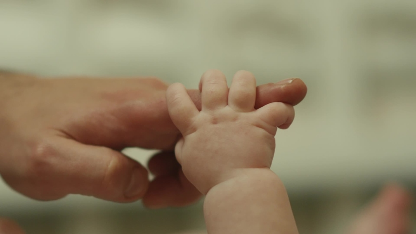 Close-up shot of baby's little cute hand reaching for father's loving finger . Baby holding parent's finger . Parent holding newborns hand in Slow Motion . Hand in hand. Father and his newborn baby .