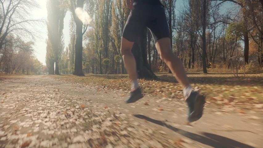 Running Man At Fall Park.Runner Man Fit Athlete Legs Jogging On Trail For Triathlon.Triathlete Running,Sprinting And Endurance Workout Training.Marathon Runner Jog On Trail.Jogger Fitness Sport Run | Shutterstock HD Video #1041348064