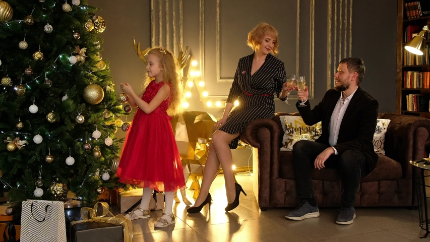 Beautiful man and woman sitting on the couch and drinking sparkling wine, and a little girl decorating the christmas tree. The family celebrates the new year at home. | Shutterstock HD Video #1041349663