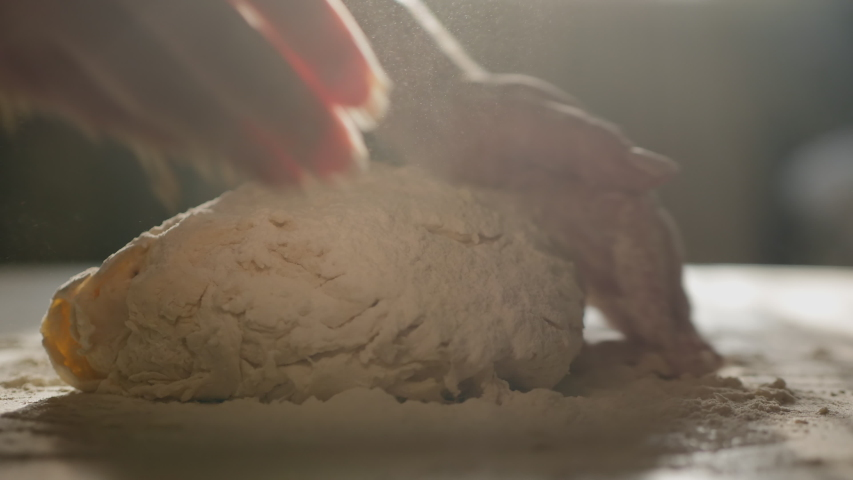 Female hands kneading dough in flour on the table, slow motion, sunlight from the window illuminates the scene.
