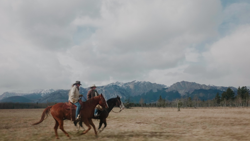 Horseback Riders Galloping Through Mountain Prairies of Canmore Alberta Canada  with Rocky Mountains in the Background Beautiful Country Style Living