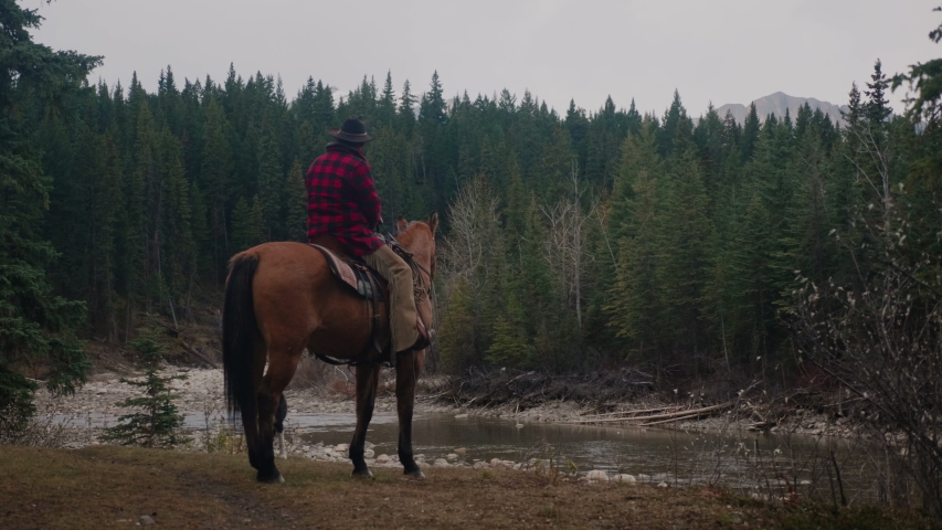 Cowboy sits on Horse Beside Creek in Alberta Mountains