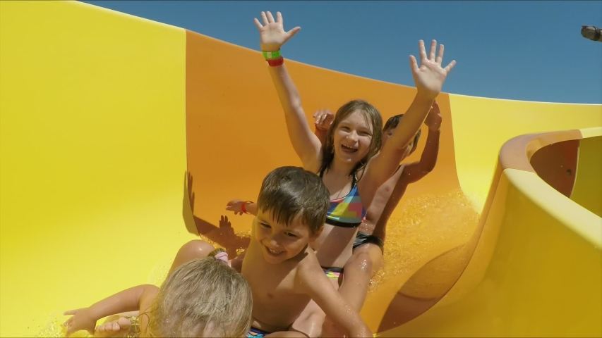 Group of children riding down an orange slide in a water park. Children laugh merrily and wave their hands