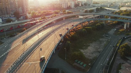 Beautiful top side view to the cars driving on multi-level highway on the sunny evening in Moscow. Picturesque aerial panorama of the road traffic and sunset city.