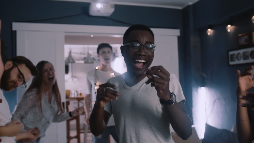 Happy young smiling African student man in eyeglasses dancing with friends at multiethnic holiday celebration party. | Shutterstock HD Video #1041382621